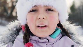Nieve que sopla sonriente de la niña almacen de metraje de vídeo