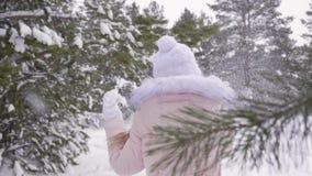 Nieve que sopla y que lanza del adolescente de la muchacha en bosque conífero en el día de invierno metrajes
