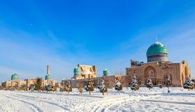 Nieve y piceas con las bóvedas y los alminares azules de Hazrati musulmán imagenes de archivo