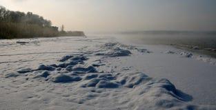 Nieves acumulada por la ventisca en un lago del invierno Foto de archivo