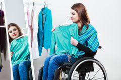 Nieważna dziewczyna na wózka inwalidzkiego wybierać odziewa w garderobie Fotografia Royalty Free