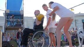 Nieważna samiec na koła krzesła dźwignięć ciężkim kettlebell z potomstwami sądzi przy wydarzeniem sportowym w świetle słonecznym zbiory