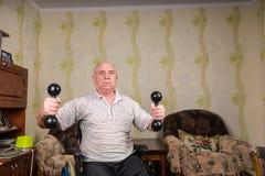 Nieważny stary człowiek robi ćwiczeniom z dumbbells zdjęcie stock
