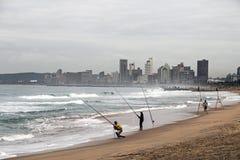 Niewiadomi rybacy na plaży przeciw Chmurzącej Durban miasta linii horyzontu Obrazy Stock