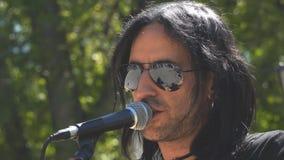 Niewiadomy piosenkarz śpiewa w mikrofon w parku zbiory wideo
