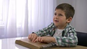 Niewidoma dziecko chłopiec czyta Braille książkę z symbol chrzcielnicą dla Wzrokowo nadwyrężonego obsiadania przy stołem zbiory wideo
