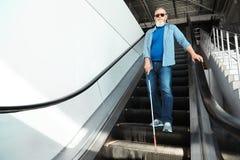 Niewidoma osoba z d?ug? trzcin? na eskalatorze indoors obrazy royalty free