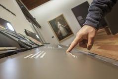 Niewidomy czytelniczy teksta podpis w Braille języku przy muzeum Fotografia Stock