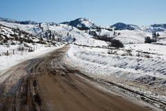 Niewygładzona droga gruntowa w zimie z śniegiem i górami obrazy royalty free