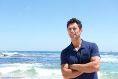 Niewygładzona w średnim wieku mężczyzna pozycja przy plażą zdjęcia stock