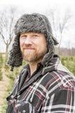 Niewygładzony outdoorsman w futerkowym kapeluszu i uszatych łopotach, outside w zimie, zdjęcie royalty free
