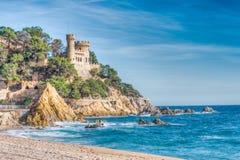 Niewygładzony skalisty wybrzeże z D'en Plaja kasztelem w tle zdjęcia stock