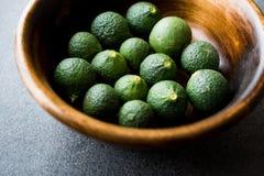 Niewyrobeni Niedojrzali Organicznie zieleni wapno w Drewnianym pucharze zdjęcia stock