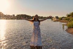 Niewyrobiona młoda dziewczyna w białej mokrej sukni stoi w rzece i kropi wodne kropelki up w promieniach powstający słońce zdjęcie royalty free