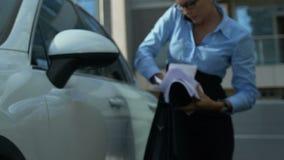 Niezdarna biznesowa kobieta dostaje z samochodu, rzuca papiery przy pracą, zły dzień zbiory