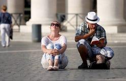 Niezdecydowani turyści dobierają się patrzeć przewodnika Zdjęcia Stock