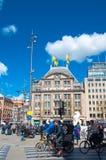 Niezdefiniowani ludzie krzyżują ulicę na rowerach na tama kwadracie, De Bijenkorf statku flagowego sklep na tle na Kwietniu 30, 2 Zdjęcia Stock