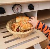 Niezdrowy dziecka jedzenie Dziecka dojechanie dla kiełbasianej chlebowej rolki w zabawce Zdjęcia Royalty Free