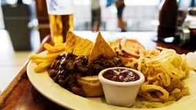 Niezdrowy posiłek z meksykańskimi nacho układami scalonymi ładował z wołowiną, ser, dłoniaki, cebulkowi pierścionki Fotografia Stock