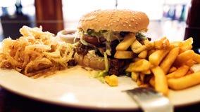 Niezdrowy posiłek z meksykańskimi nacho układami scalonymi, wołowina hamburger, ładował z serem, dłoniaki, cebulkowi pierścionki Fotografia Stock