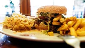 Niezdrowy posiłek z meksykańskimi nacho układami scalonymi, wołowina hamburger, ładował z serem, dłoniaki, cebulkowi pierścionki Obrazy Stock