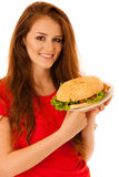 Niezdrowy posiłek - szczęśliwa młoda kobieta je hamburger odizolowywającego Fotografia Stock