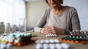 Niezdrowy starszy damy cierpienia ból patrzeje pigułki, środka przeciwbólowego śledziennictwo zdjęcia stock