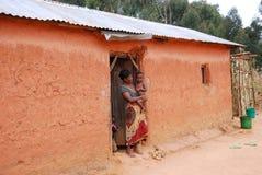 Niezidentyfikowana Afrykańska kobieta z jej dziećmi na progu Fotografia Royalty Free