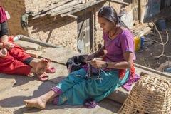 Niezidentyfikowana dziewczyna szy suknię w podwórku na Grudniu 2, Zdjęcie Stock