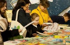 Niezidentyfikowana dziewczyna z macierzystymi dopatrywanie nowymi książkami książkowy festiwal Obrazy Stock