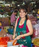 Niezidentyfikowana kobieta sprzedaje marchewki i pakuje one w plastikowych workach Obraz Stock