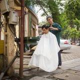 Niezidentyfikowanego fryzjera męskiego rżnięty włosy na ulicie Fotografia Stock