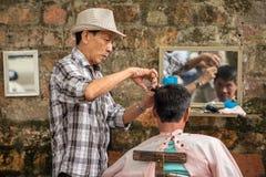 Niezidentyfikowanego fryzjera męskiego rżnięty włosy na ulicie Hanoi Obrazy Royalty Free