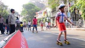 Niezidentyfikowani dzieci Kolkata miasta rollerskating na blokującej drodze, India zbiory