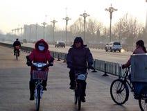 Niezidentyfikowani ludzie jedzie rowery i odprowadzenie obok ruchu drogowego w wczesnego poranku smogu zdjęcie stock