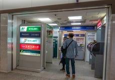 Niezidentyfikowani ludzie stać w kolejce przy ATM maszynami przy Osaka miasta dworcem obraz stock
