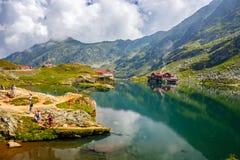 Niezidentyfikowani turyści cieszą się widoki Balea jezioro przy 2.034 m wysokością w Fagaras górach Zdjęcie Stock
