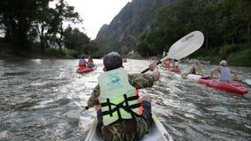 Niezidentyfikowani turyści kayaking wzdłuż Nam Pieśniowej rzeki w Vang Vieng miasteczku zdjęcie wideo