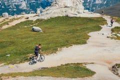 Niezidentyfikowany rowerzysta wspina się wzgórze w Bucegi górach w Rumunia Obraz Royalty Free