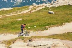Niezidentyfikowany rowerzysta wspina się wzgórze w Bucegi górach w Rumunia Fotografia Royalty Free