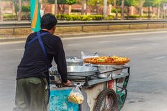 Niezidentyfikowany uliczny domokrążca pcha mobilną kuchenną furę na st Obraz Royalty Free