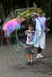 Niezidentyfikowany wykonawca i dzieciaki bawić się z mydlanymi bąblami przy Centra Fotografia Stock