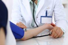 Nieznane doktorska kobieta sprawdza ci?nienie krwi ?e?ski pacjent, w g?r? Kardiologia w medycyny i opieki zdrowotnej poj?ciu fotografia stock