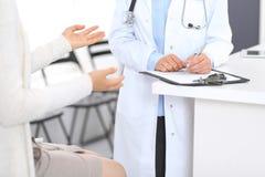 Nieznane doktorski i żeński pacjent dyskutuje coś podczas gdy stojący blisko recepcyjnego biurka w przeciwawaryjnym hospit fotografia royalty free