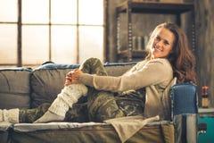 Niezobowiązująco ubierający kobiety obsiadanie na kanapy ono uśmiecha się Fotografia Stock