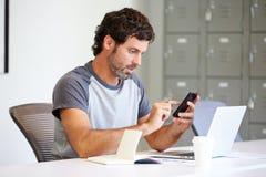 Niezobowiązująco Ubierający mężczyzna Używa telefon komórkowego W projekta studiu Zdjęcia Stock