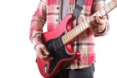Niezobowiązująco ubierający młody człowiek z gitarą bawić się piosenki odizolowywać na bielu tabela laptopa Online gitar lekcj po Fotografia Stock