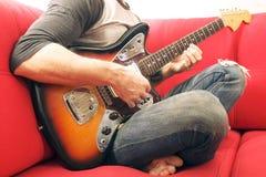 Niezobowiązująco ubierający młody człowiek z gitarą bawić się piosenki w pokoju w domu Online gitar lekcj pojęcie Męski gitarzyst fotografia stock