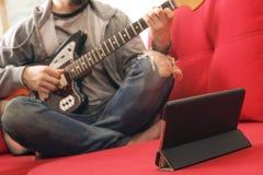 Niezobowiązująco ubierający młody człowiek z gitarą bawić się piosenki w pokoju w domu Online gitar lekcj pojęcie Męski gitarzyst zdjęcie stock