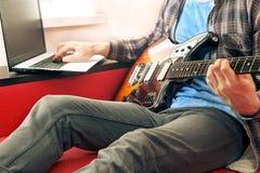 Niezobowiązująco ubierający młody człowiek z gitarą bawić się piosenki w pokoju w domu Online gitar lekcj pojęcie Męski gitarzyst zdjęcia royalty free